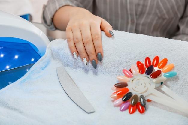 Женщина с искусственными акриловыми ногтями подбирает новый цвет лака во время процедуры маникюра. процесс маникюра в салоне красоты на белом полотенце. гигиеническая красота рук в маникюрном салоне.