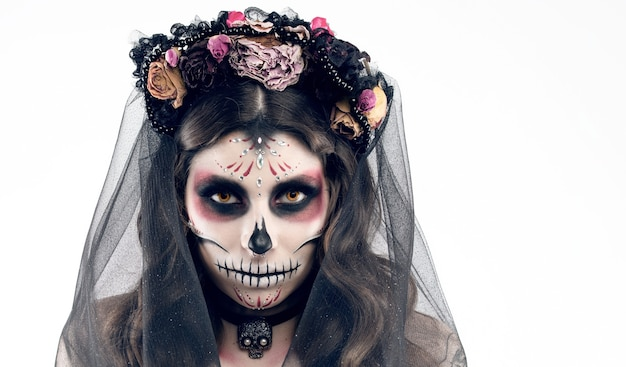 Woman with artistic spooky makeup and fresh flowers on head standing prepared for halloween party