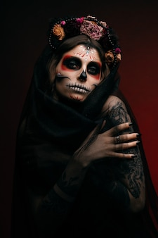 Woman with artistic spooky makeup and fresh flowers on head standing prepared for halloween