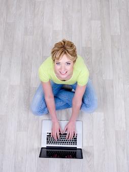 床にラップトップを使用して魅力的な笑顔を持つ女性-ハイアングル