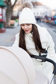 Woman with baby in carriage outside