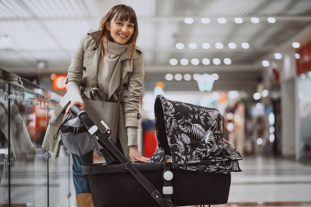 Woman with baby carriage in shopping mall