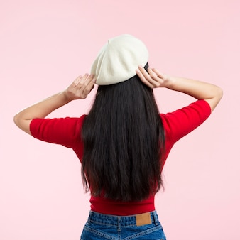 Woman with back fixing her hat