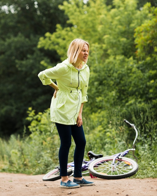 Woman with back pain and fallen bicycle