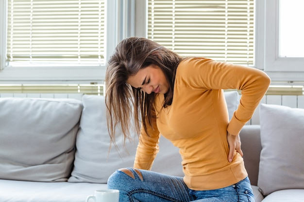 Woman with a back pain sitting on the sofa