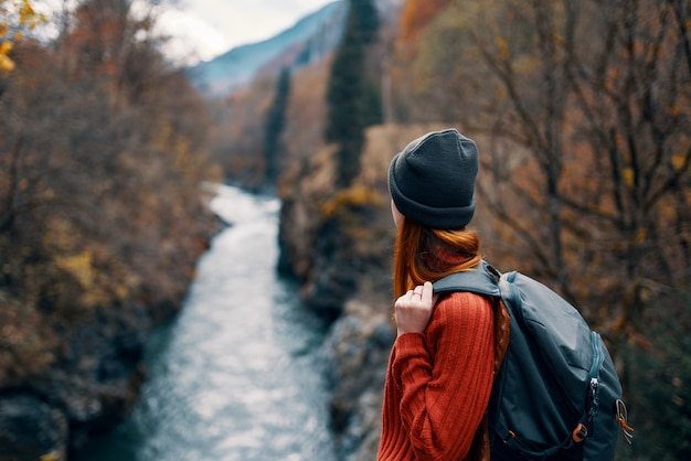 Woman with backpack admires the river in the mountains nature travel