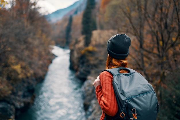 バックパックを持った女性は山の自然旅行で川を賞賛します