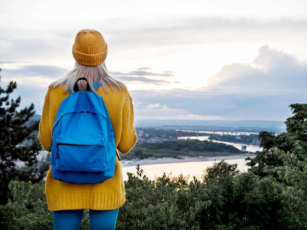 Woman with backpack admiring mountain view