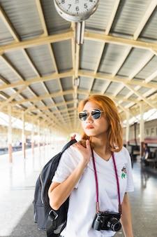 Женщина с рюкзаком и камерой на складе