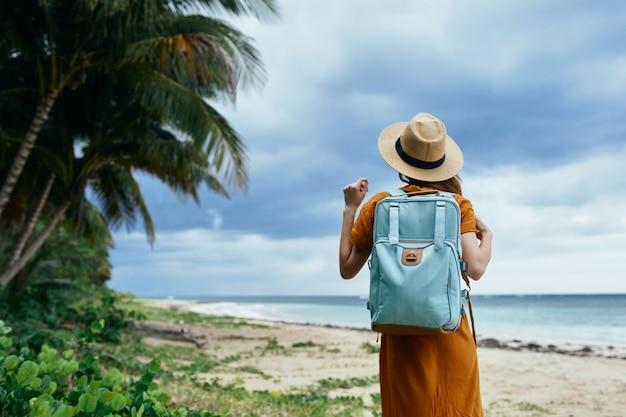 海の上のバックパックと帽子の砂浜の島の背の高い木を持つ女性