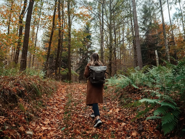 Woman with a backpack in the autumn forest