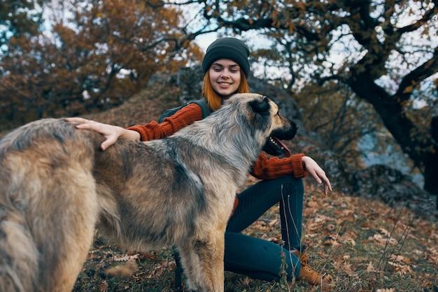 犬の友情自然旅行休暇の横にバックパックを持つ女性