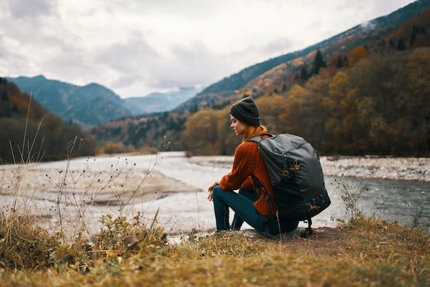 川の山の風景秋の乾いた草モデルでバックパックを持つ女性