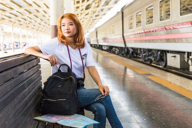 Woman with backpack and camera on bench on depot