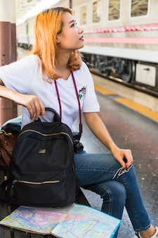 Woman with backpack and camera on bench on platform
