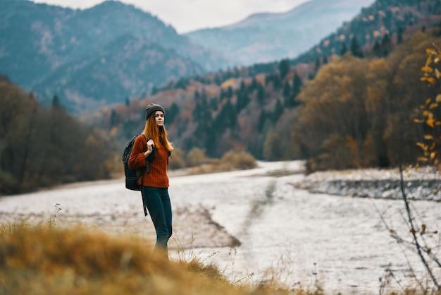 山の風景の中の川でハイキングをするバックパックを持つ女性