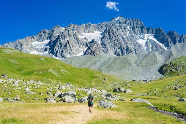 Woman with backpack hiking towards mountain top, scenic glacier and dramatic landscape summer fitness