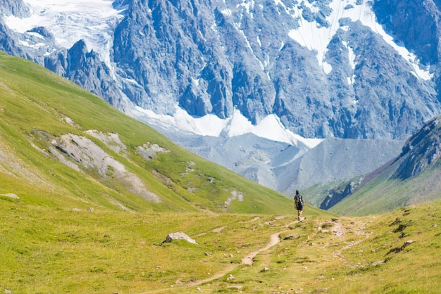 山頂に向かってハイキングバックパックを持つ女性