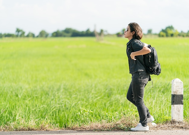 Woman with backpack hitchhiking along a road