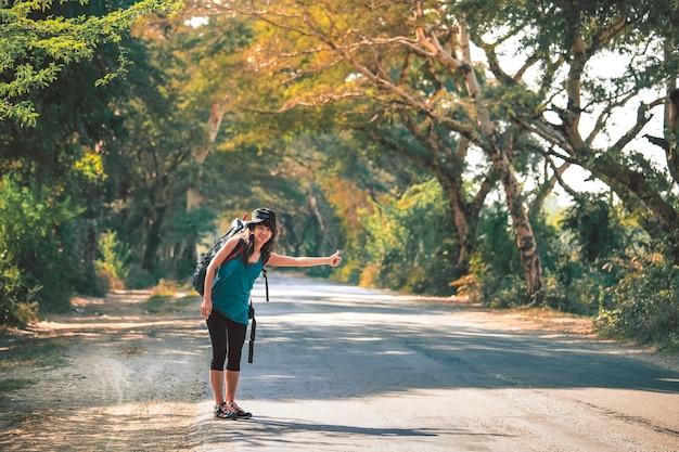 ミャンマー、バガンの田舎道でヒッチハイクのバックパックを持つ女性