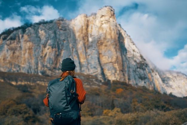ジャケット秋の旅行山でバックパックを持つ女性