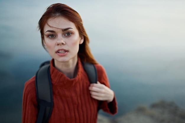 海の近くの屋外の山でバックパックを持っている女性は、トリミングされたビューモデルを引き返しました。高品質の写真