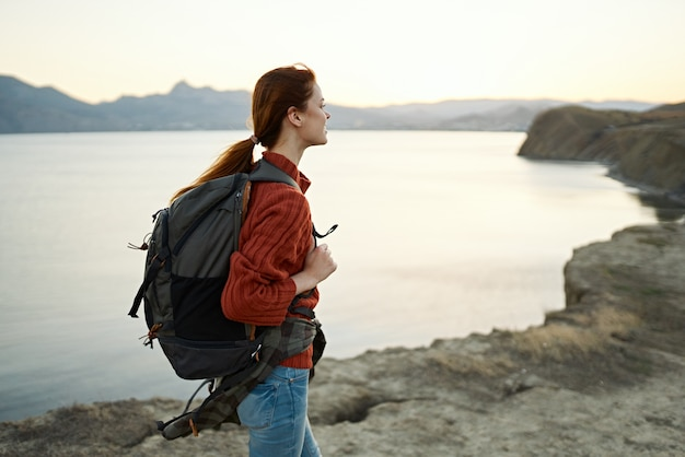 山のバックパックを持つ女性は旅行の冒険の自由を歩きます
