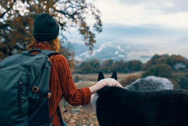 自然の中でバックパックを持つ女性は、山の風景の中で犬と遊ぶ。高品質の写真