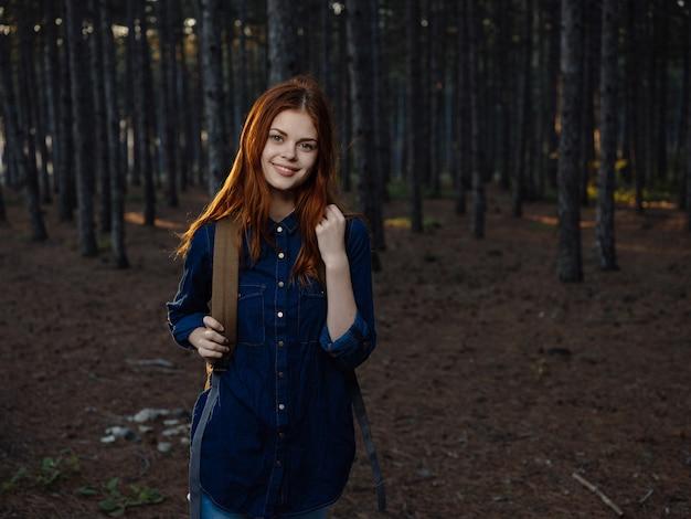 森の旅の冒険休暇でバックパックを持つ女性