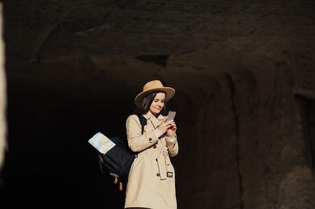 배낭을 메고 스마트폰을 사용하는 여성