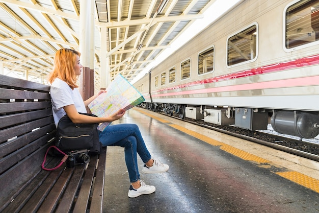 Woman with backpack and map on bench on platform