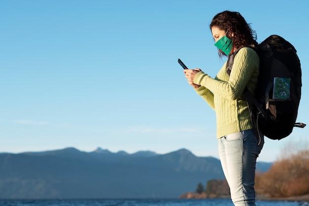 Женщина с рюкзаком на спине и в маске использует свой мобильный телефон для отправки сообщений возле озера
