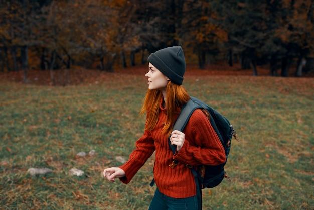 背中にバックパックを背負った女性 ハイキング トラベル ハット セーター モデル