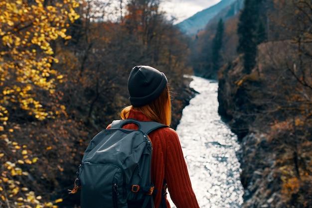 Женщина с рюкзаком на ее спине река горы природа путешествия