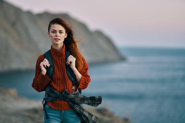 彼女の背中にバックパックを持つ女性旅行観光セーター海海の山々。高品質の写真