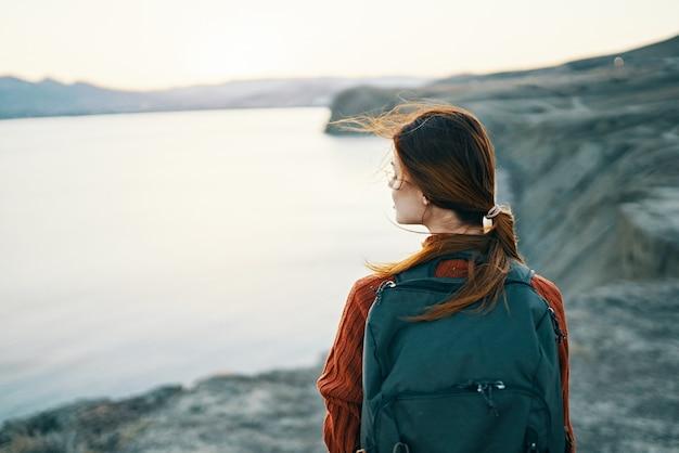 日没時の海の近くの山の自然にバックパックを持つ女性