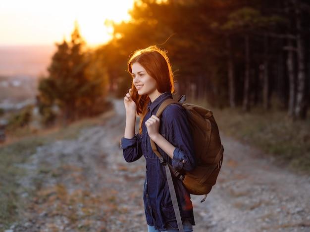 自然の散歩休暇の山にバックパックを持つ女性