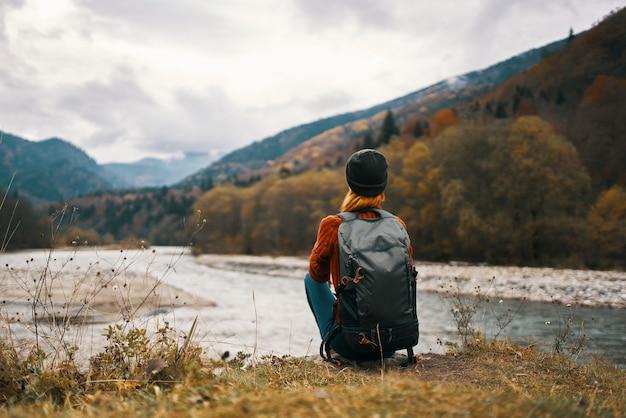 川の土手にバックパックを持つ女性は、背景の山の風景を賞賛します