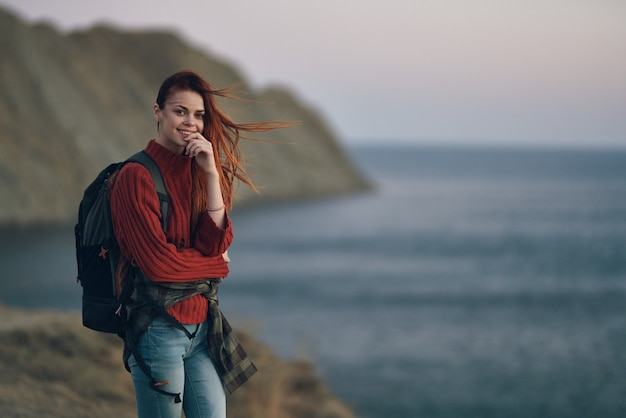 Woman with backpack red sweater model and mountains ocean nature