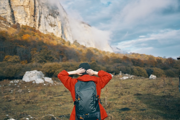 Woman with a backpack red sweater warm hat landscape autumn fallen leaves model
