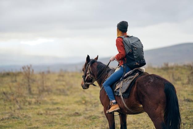 バックパックに乗って馬の自然散歩友情を持つ女性