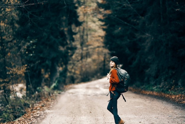Woman with backpack on the road in the forest in autumn landscape tall trees model