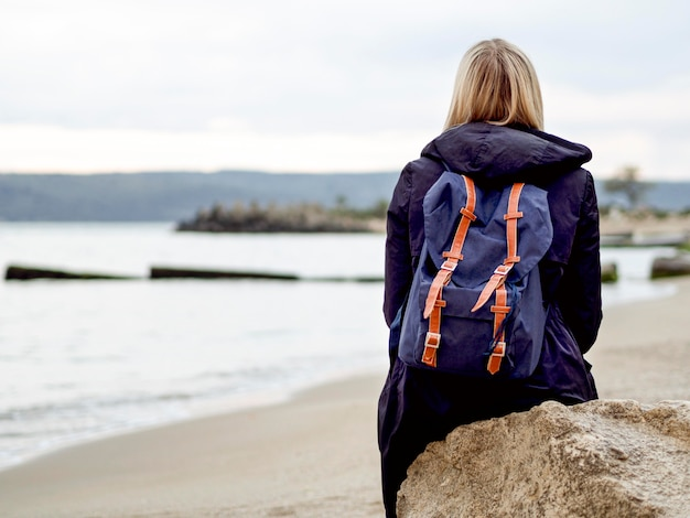 Woman with backpack at sea shore