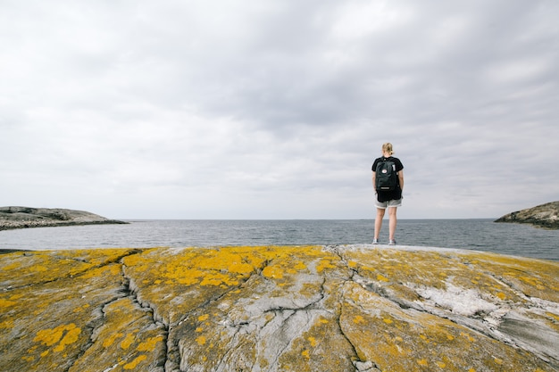 Woman with a backpack standing on a rock near the sea with a cloudy sky