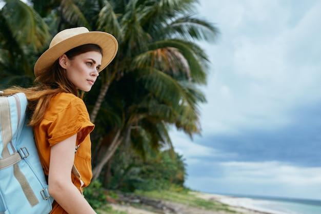 バックパックを持った女性が島の緑の葉の休暇を旅行します