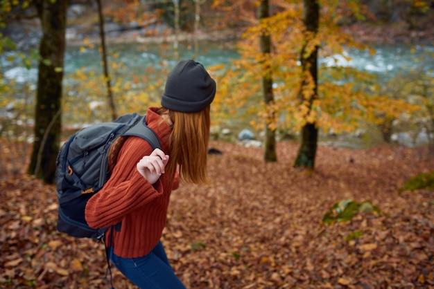 バックパックを持った女性が秋の森を旅します。高品質の写真