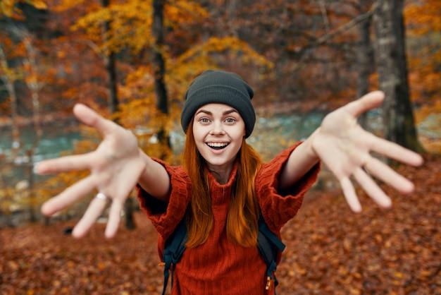 バックパックを持った女性が秋の森を旅する