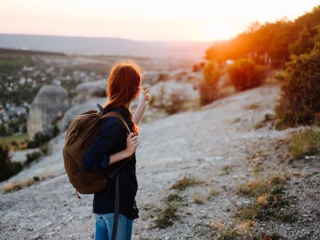 バックパック旅行山サンセット自然ライフスタイルを持つ女性