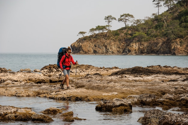Woman with backpack travelling on sea coast