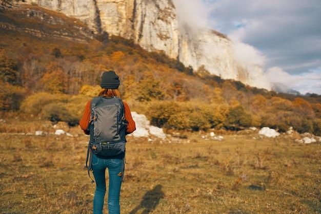 バックパックを持つ女性は自然の中を旅し、山に登る